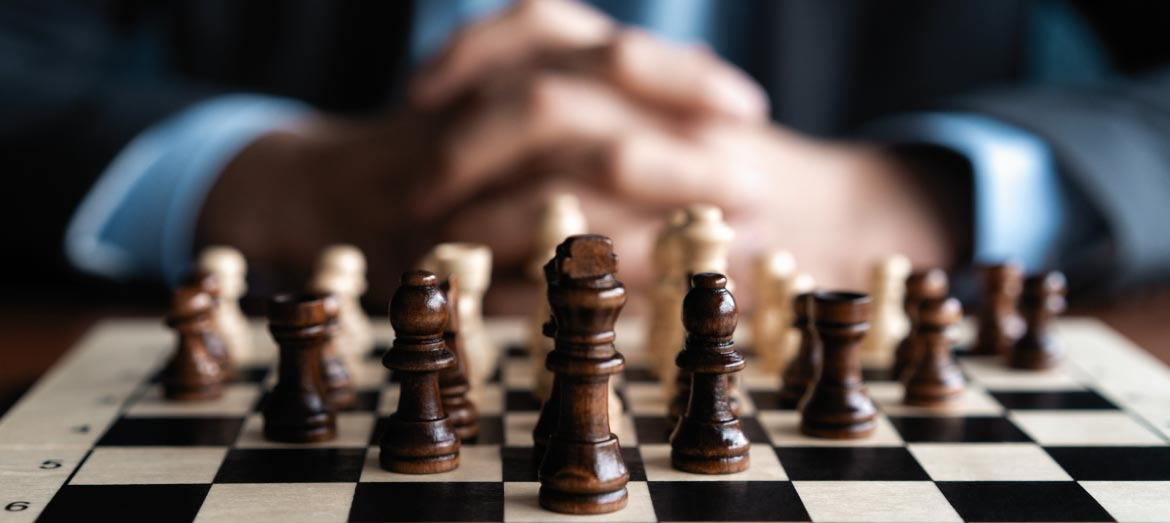 Providior Insights - man clasping hands behind chess pieces
